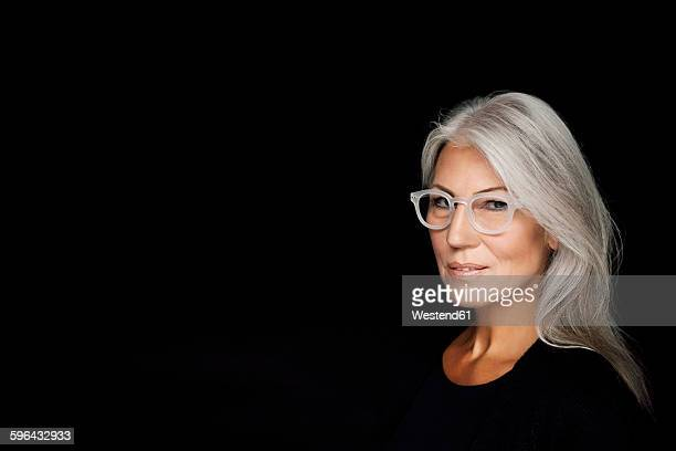 Portrait of mature woman with grey hair wearing glasses in front of black background