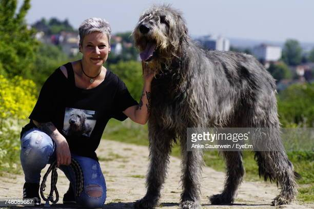 Portrait Of Mature Woman With Irish Wolfhound On Footpath During Sunny Day