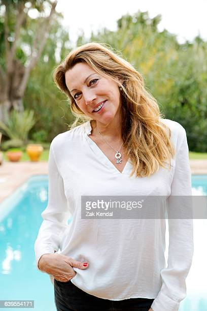 Portrait of mature woman with long blond hair with hand in pocket in front of swimming pool