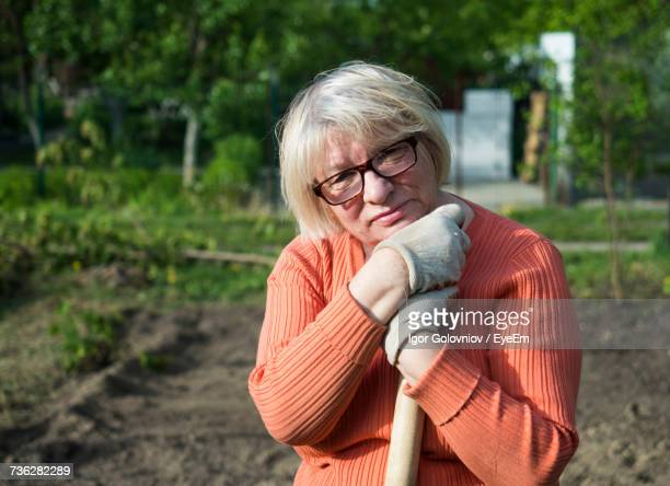 Portrait Of Mature Woman With Shovel Standing At Yard