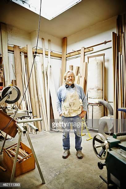 Portrait of mature woodworker standing in woodshop