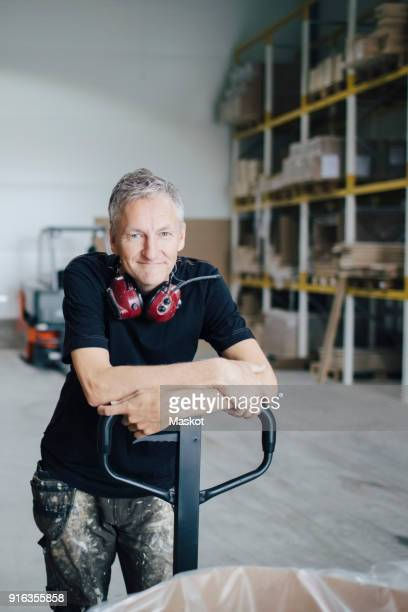 portrait of mature worker leaning on pallet jack by stack at industry - hoch allgemeine beschaffenheit stock-fotos und bilder