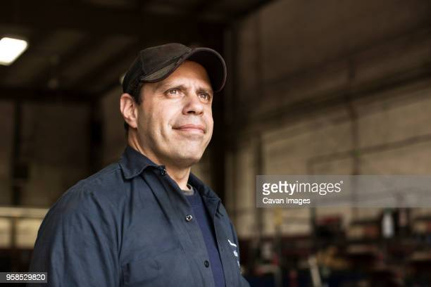portrait of mechanic standing by bus in repair shop - handwerker stock-fotos und bilder