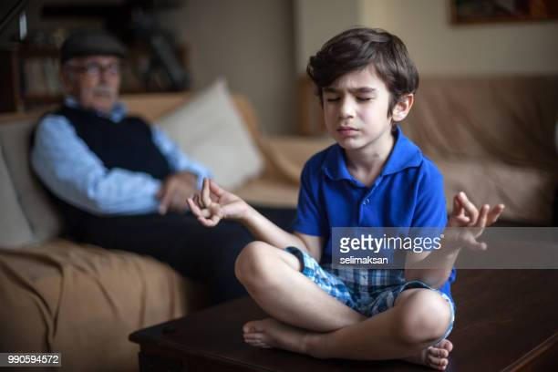 Portrait Of Meditating Grandson And Grandfather