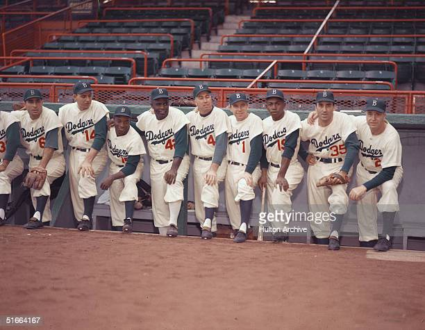 Portrait of members of the Brooklyn Dodgers baseball team pose in the dugout, 1954. From left, Americans Carl Furillo and Gil Hodges , Cuban Sandy...