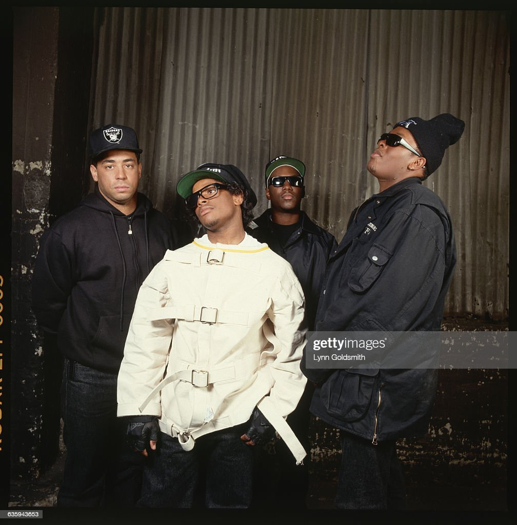 Portrait of members of the rap group, NWA, including DJ Yella, MC Ren, Eazy-E (center, wearing straitjacket), and Dr. Dre (right, wearing ski cap).