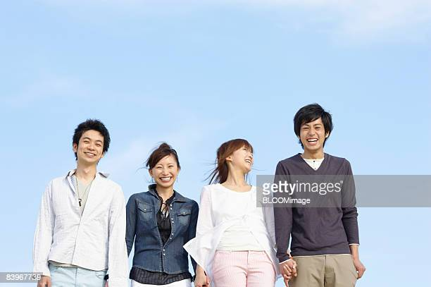Portrait of men and women standing hand in hand against blue sky, smiling