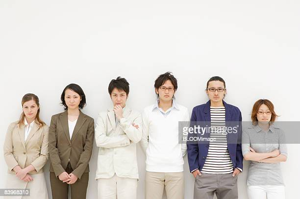 Portrait of men and women standing in a row with serious expression