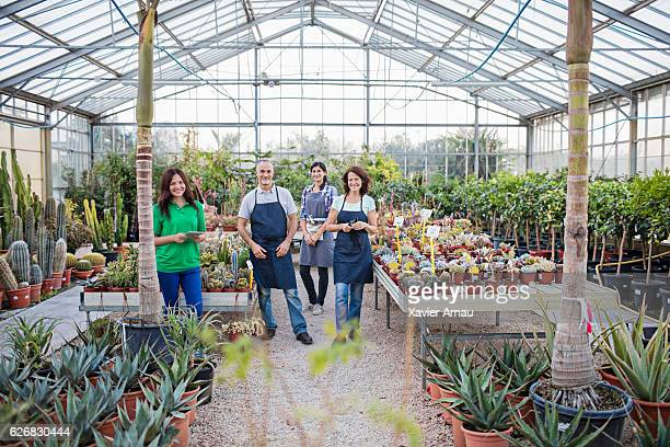 Portrait of men and women standing in greenhouse