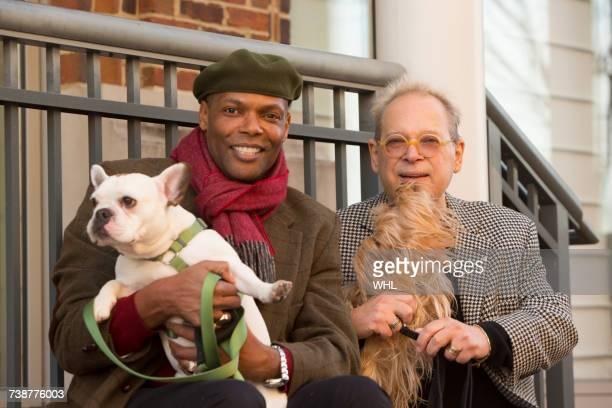 Portrait of men sitting on stoop holding dogs