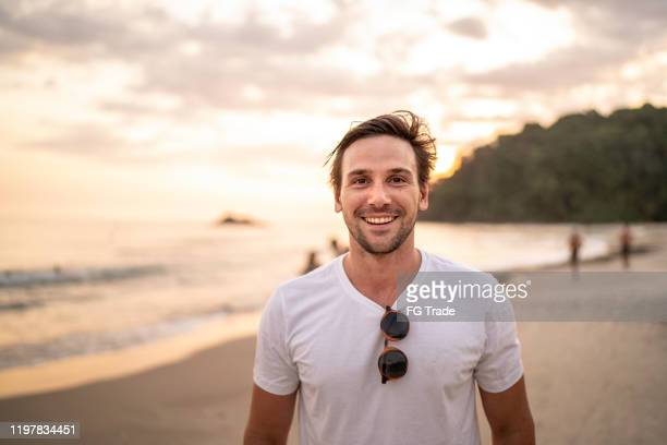 portrait of men smiling at the beach - one man only stock pictures, royalty-free photos & images
