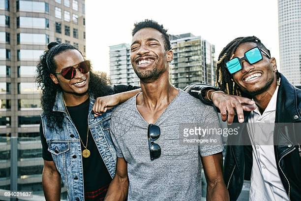 Portrait of men smiling on urban rooftop