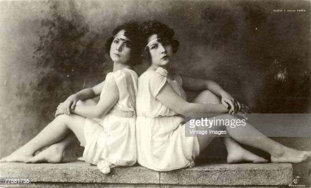 Portrait of Mexican actress sisters Alicia and Celia Perez as they pose in similar outfits based on ancient Greek and Roman clothing and sit back to...