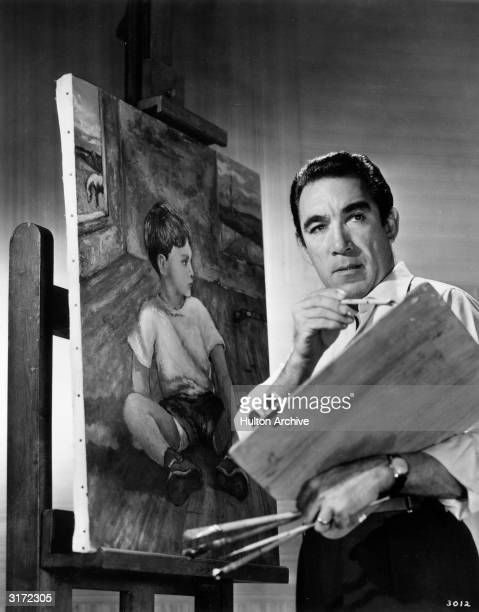 Portrait of Mexicanborn actor Anthony Quinn working on his original oil painting of his son Duncan He is wearing an oxford shirt with the sleeves...