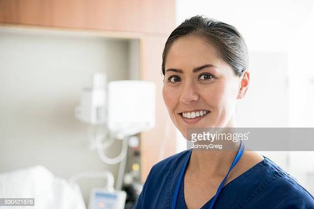Portrait of mid adult Asian nurse smiling towards camera