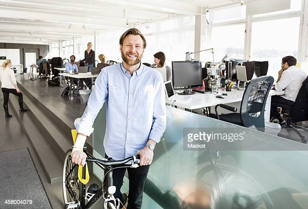 Portrait of mid adult businessman holding bicycle with colleagues working in background at office