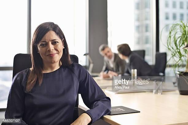 Portrait of mid adult businesswoman at office desk