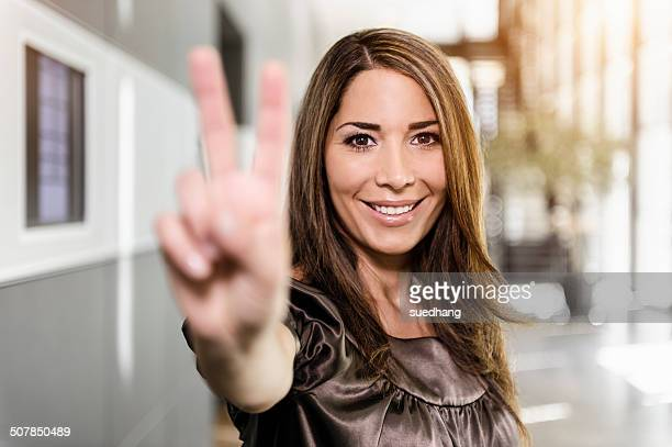Portrait of mid adult businesswoman holding up hand in victory sign