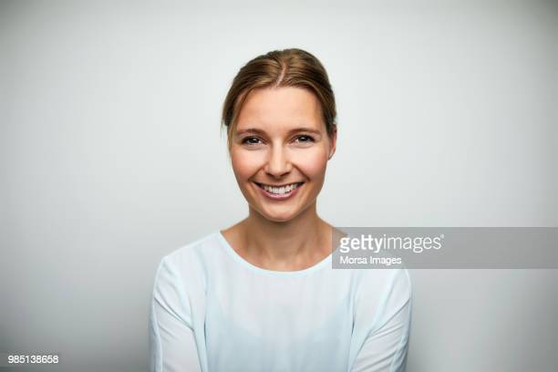 portrait of mid adult businesswoman smiling - frontaal stockfoto's en -beelden