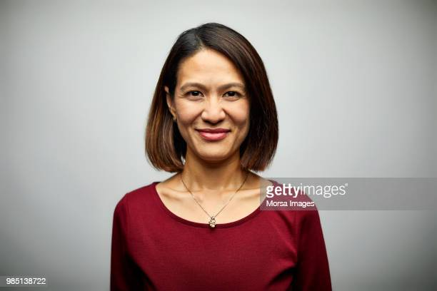 portrait of mid adult businesswoman smiling - asian and indian ethnicities stock pictures, royalty-free photos & images