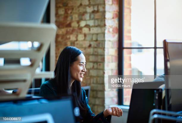 portrait of mid adult chinese woman working at desk - creative director stock pictures, royalty-free photos & images