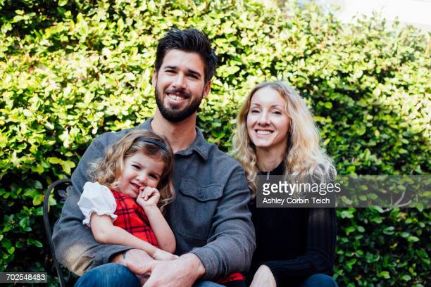 Portrait of mid adult couple and toddler daughter by garden hedge