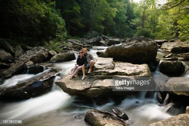 portrait of mid adult couple, sitting together on rock in waterfall, new river gorge national river, fayetteville, west virginia, usa - fayetteville stock pictures, royalty-free photos & images