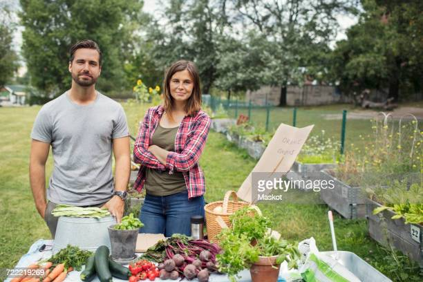 Portrait of mid adult couple standing at table full of freshly harvested garden vegetables