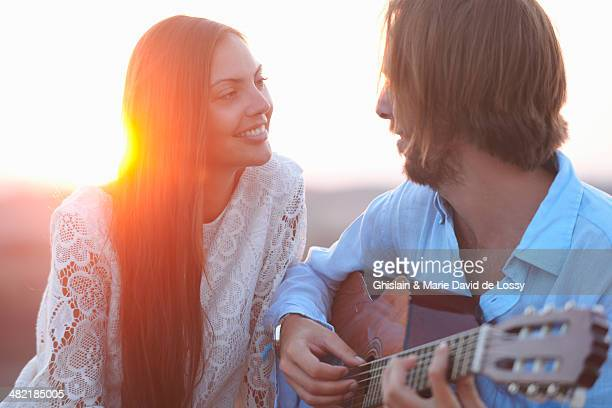 Portrait of mid adult couple with acoustic guitar