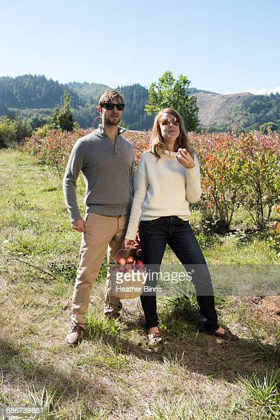 Portrait of mid adult couple with basket of picked apples in organic farm orchard