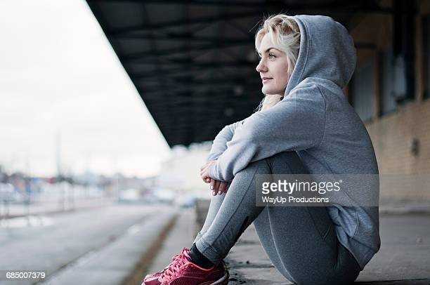 Portrait of mid adult female runner in grey hoody, sitting gazing