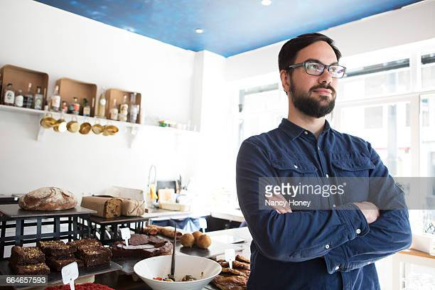 Portrait of mid adult male cafe owner at kitchen counter
