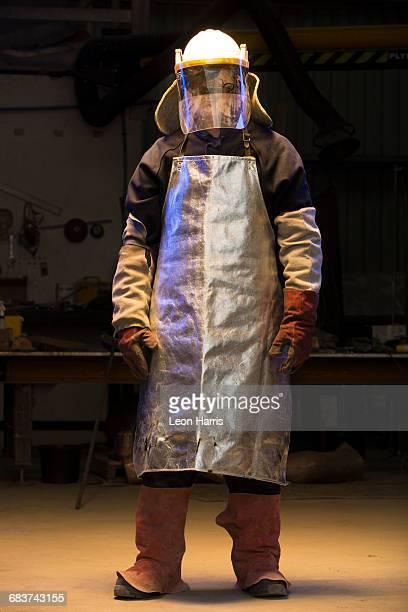 Portrait of mid adult male foundry worker wearing welding mask visor in bronze foundry