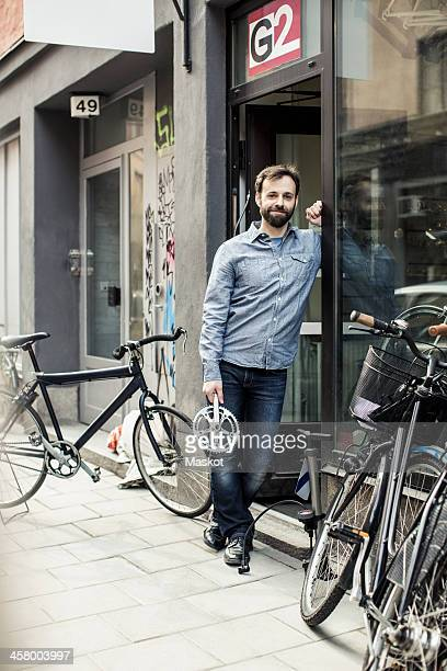 Portrait of mid adult male owner with pedal standing at the doorway of bicycle repair shop