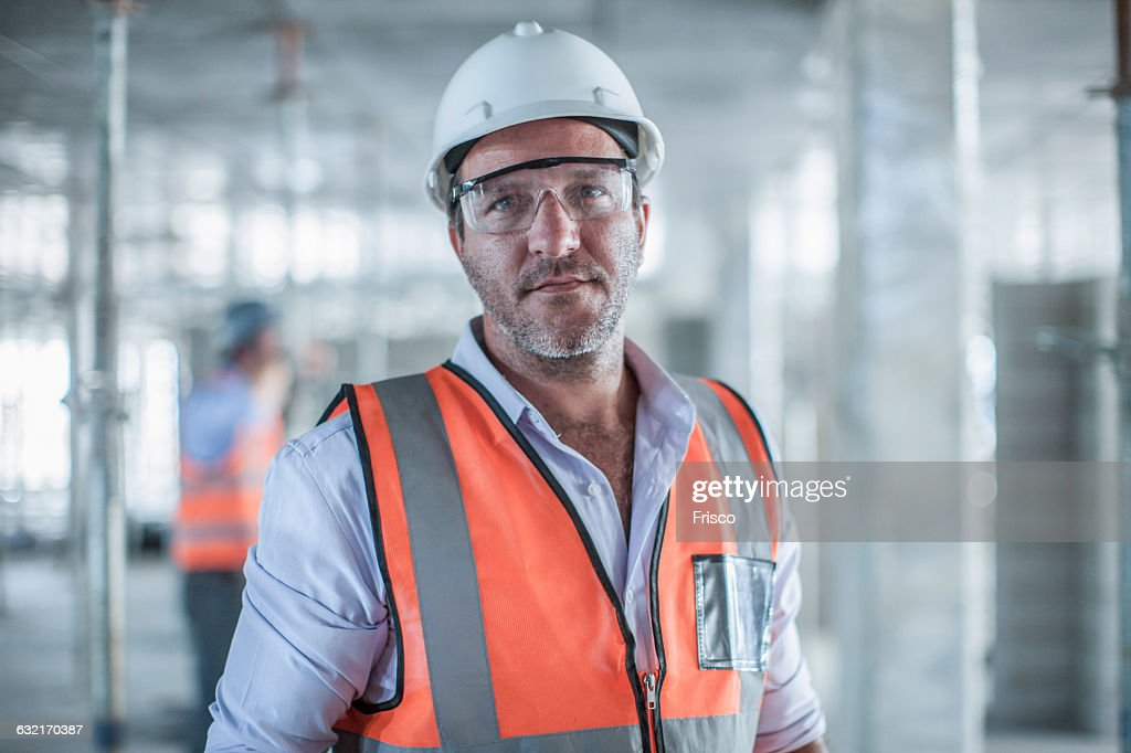 Portrait of mid adult male site manager on construction site : Stock Photo
