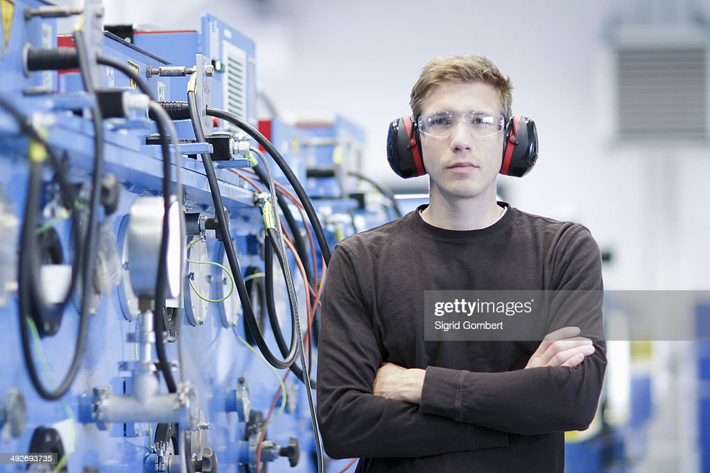 Portrait of mid adult male wearing ear protectors in engineering plant : Stock-Foto