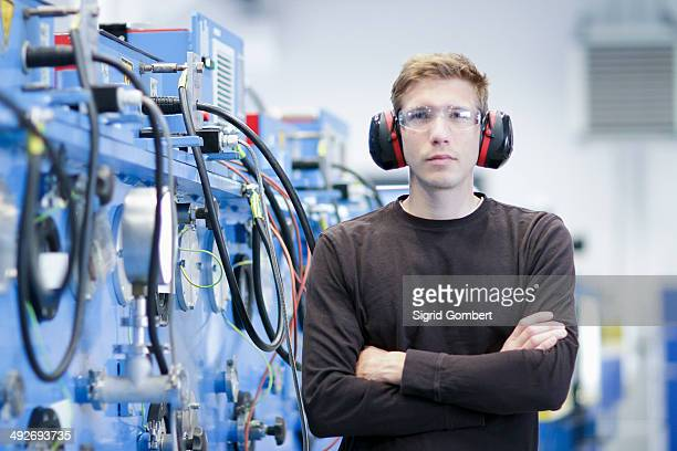 Portrait of mid adult male wearing ear protectors in engineering plant