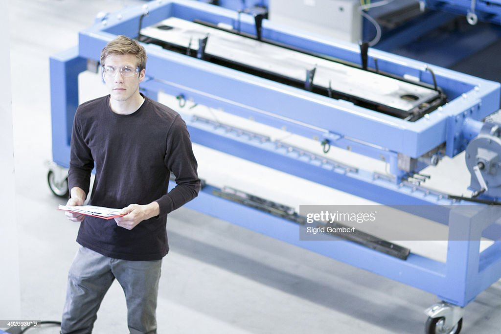 Portrait of mid adult male with paperwork in engineering plant : Stock-Foto