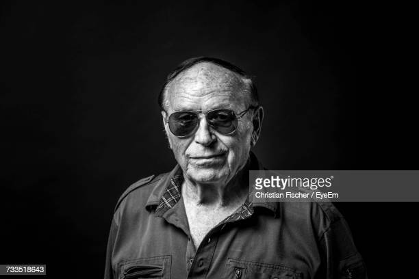 portrait of mid adult man against black background - toughness stock pictures, royalty-free photos & images
