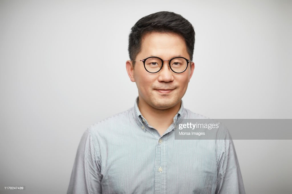 Portrait of mid adult man against white background : Stockfoto