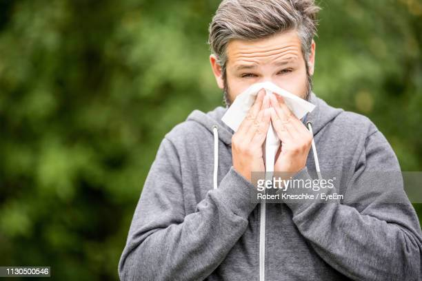 portrait of mid adult man blowing nose with tissue while standing against trees in park - handkerchief photos et images de collection