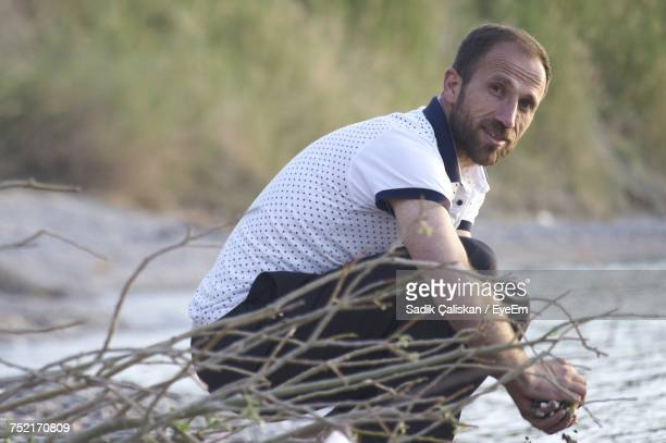 Portrait Of Mid Adult Man Collecting Stones While Crouching At Beach