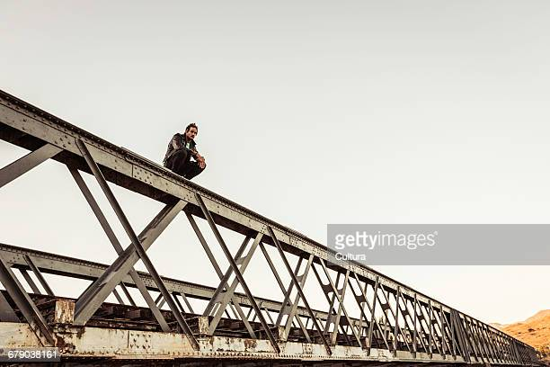 Portrait of mid adult man crouching on top of rural railway bridge, Franschhoek, South Africa
