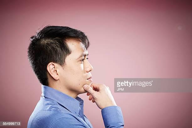 portrait of mid adult man, hand on chin - あご ストックフォトと画像