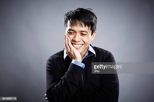 portrait of mid adult man, hand on chin, smiling - あご ストックフォトと画像
