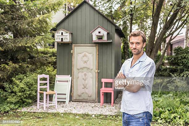 Portrait of mid adult man in front of garden shed