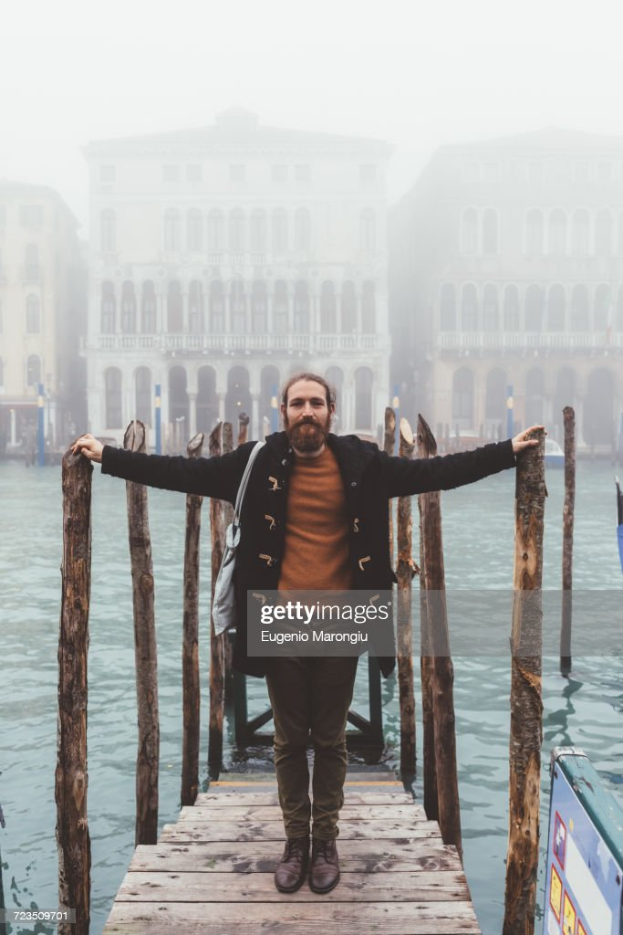 Portrait of mid adult man on misty canal pier, Venice, Italy : ストックフォト