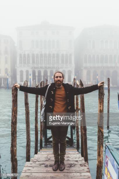 portrait of mid adult man on misty canal pier, venice, italy - ダッフルコート ストックフォトと画像