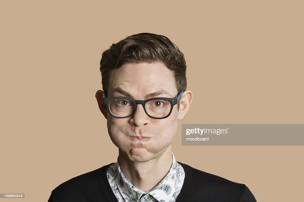 Portrait of mid adult man puffing cheeks over colored background : Foto de stock