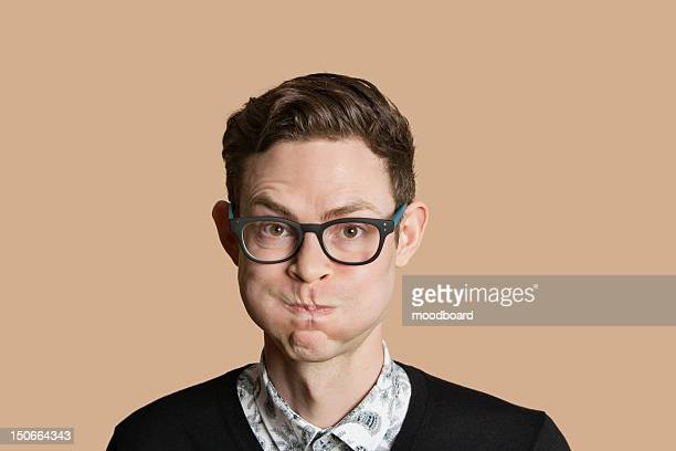 Portrait of mid adult man puffing cheeks over colored background